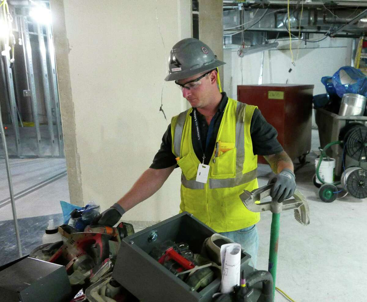 """Electrician John Hopper rummages through tools at the AT&T Center on Wednesday, Oct. 28, 2015, where renovations are wrapping up ahead of the Spurs home opener on Friday. Hopper, who has a criminal past, got his job at the county-sponsored """"Second Chance Job Fair"""" at the arena earlier this year."""