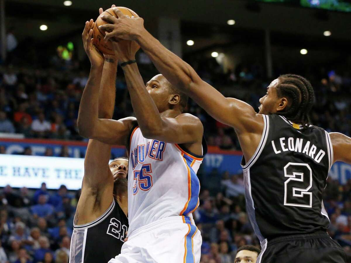 Oklahoma City Thunder forward Kevin Durant (35) is double-teamed by San Antonio Spurs forward Tim Duncan (21) and forward Kawhi Leonard (2) in the second quarter of an NBA basketball game in Oklahoma City, Wednesday, Oct. 28, 2015. (AP Photo/Sue Ogrocki)