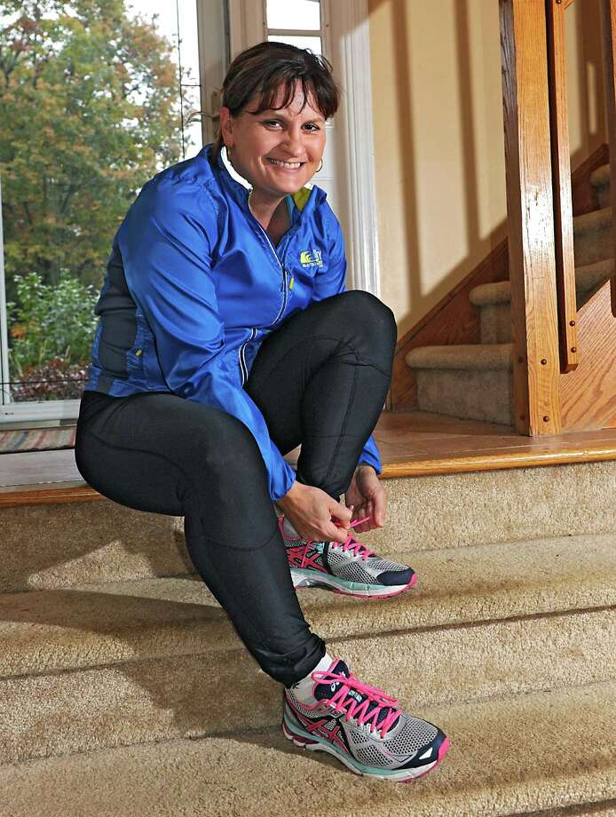 Linda Carignan laces up her shoes to go for a run on Wednesday, Oct. 28, 2015 in Schenectady, N.Y. She will be running the NYC marathon this weekend while still continuing radiation treatments for breast cancer. (Lori Van Buren / Times Union) Photo: Lori Van Buren / 00033956A