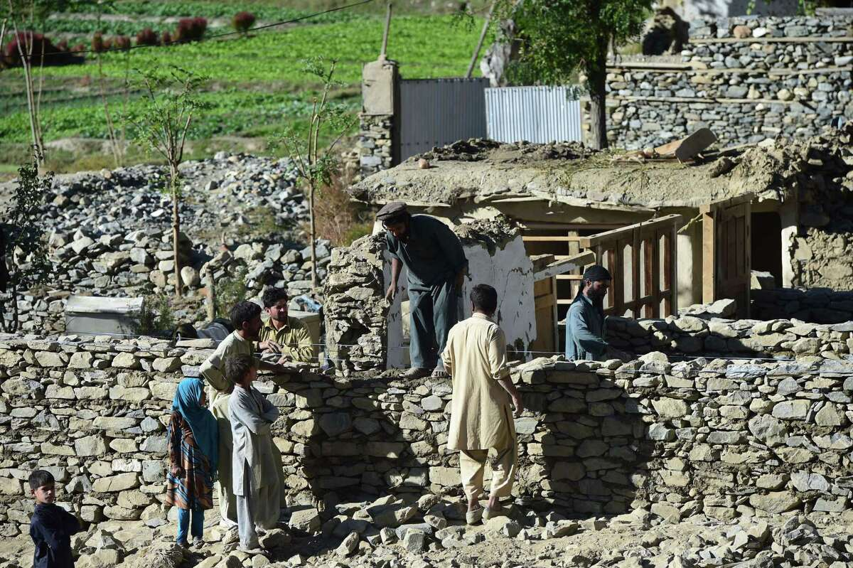 Afghan refugees earthquake survivors rebuild their house in Kesu village, some 15 km from Chitral on October 28, 2015. Digging through the rubble of an earthquake rubble less than three months after being devastated by floods, residents of the northwestern Pakistan district of Chitral cannot afford to wait for government help. AFP PHOTO / FAROOQ NAEEMFAROOQ NAEEM/AFP/Getty Images
