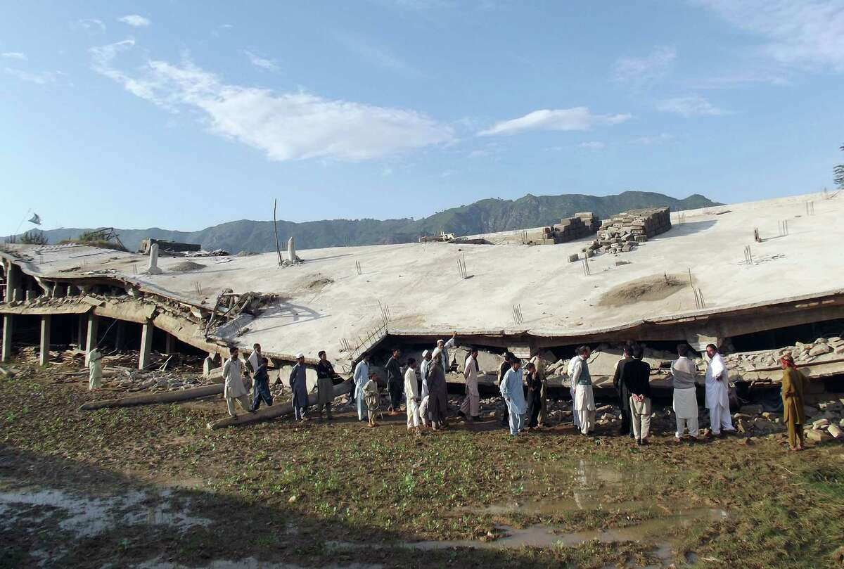 TOPSHOTS Pakistani residents gather beside a collapsed building following an earthquake in the Koga area in Buner district on October 28, 2015. Rescuers raced against time to reach cold and hungry survivors of an earthquake that left entire communities in Afghanistan and Pakistan marooned in remote mountainous regions, as the death toll climbed to 370. AFP PHOTO / Imran BUNERIIMRAN BUNERI/AFP/Getty Images