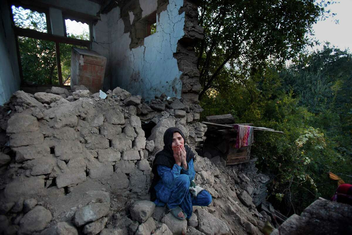 A Pakistani woman, who lost her two grandsons in Monday's earthquake, mourns as she sits on the rubble of her destroyed home, in Jinjara village in Chitral, a district of Northern Pakistan, Wednesday, Oct. 28, 2015. Afghanistan and Pakistan were scrambling Wednesday to rush aid to survivors of this week's magnitude-7.5 earthquake as the region's overall death toll from the temblor rose more than 380. (AP Photo/Anjum Naveed)
