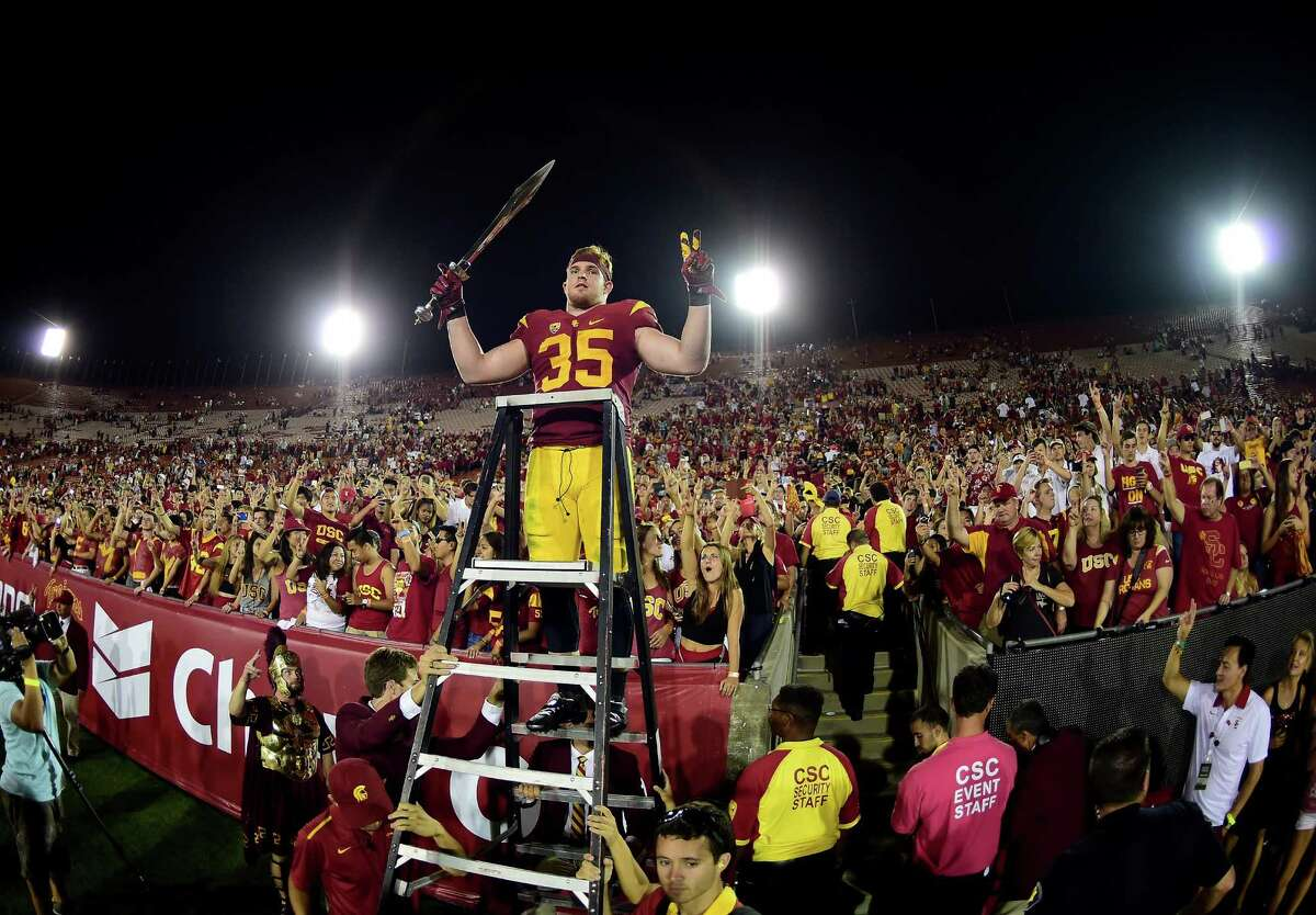 LOS ANGELES, CA - OCTOBER 24: Cameron Smith #35 of the USC Trojans celebrates a 42-24 win over the Utah Utes with fans after his three interception game at Los Angeles Memorial Coliseum on October 24, 2015 in Los Angeles, California. (Photo by Harry How/Getty Images) *** BESTPIX ***