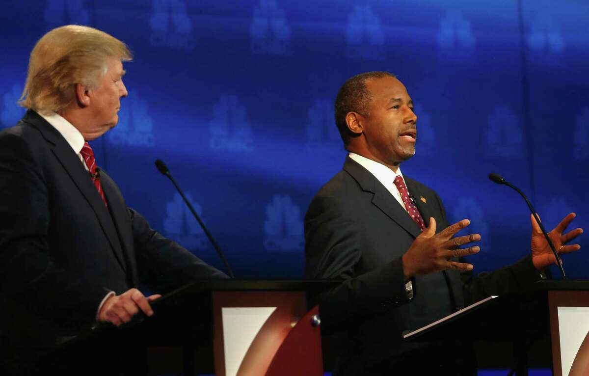 Carson speaks while Trump looks on during the debate. Carson has overtaken Trump in some recent polls.