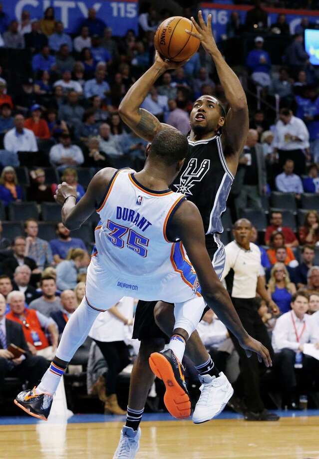 San Antonio Spurs forward Kawhi Leonard, right, is fouled by Oklahoma City Thunder forward Kevin Durant (35) while shooting in the third quarter of an NBA basketball game in Oklahoma City, Wednesday, Oct. 28, 2015. Oklahoma City won 112-106. (AP Photo/Sue Ogrocki) Photo: Sue Ogrocki, Associated Press / AP