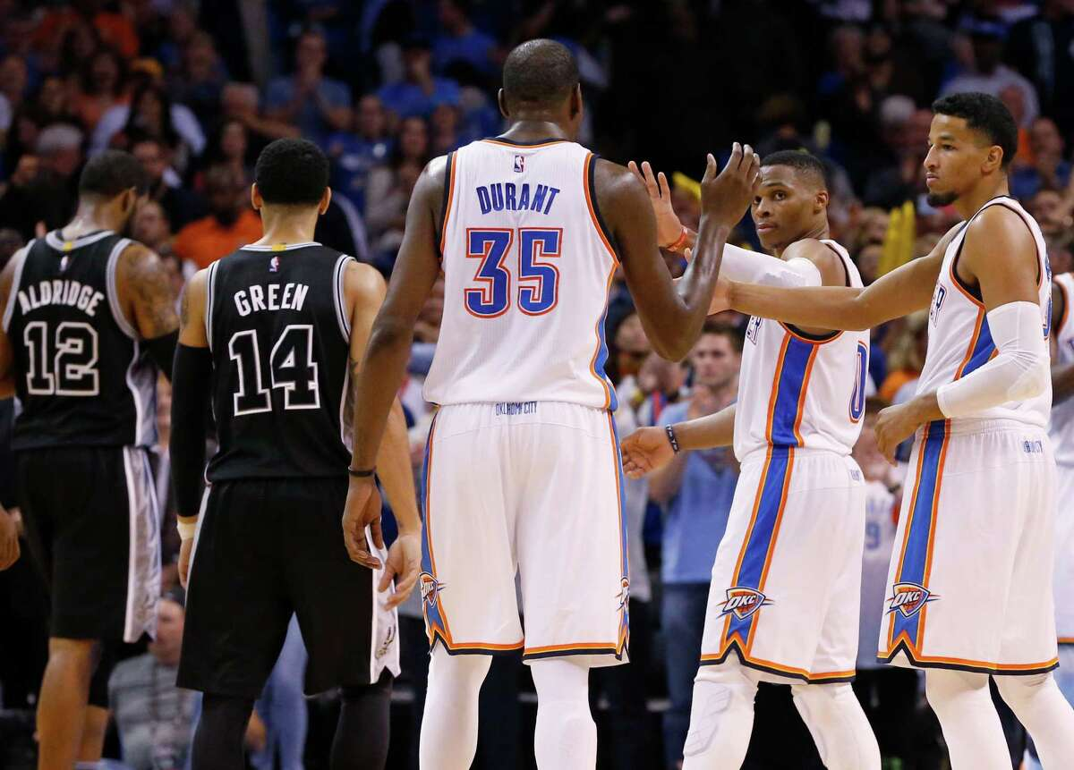 Oklahoma City Thunder forward Kevin Durant (35), guard Russell Westbrook, center, and guard Andre Roberson, right, exchange high-fives in the fourth quarter of an NBA basketball game against the San Antonio Spurs in Oklahoma City, Wednesday, Oct. 28, 2015. Spurs forward LaMarcus Aldridge (12) and guard Danny Green (14) look on. Oklahoma City won 112-106. (AP Photo/Sue Ogrocki)