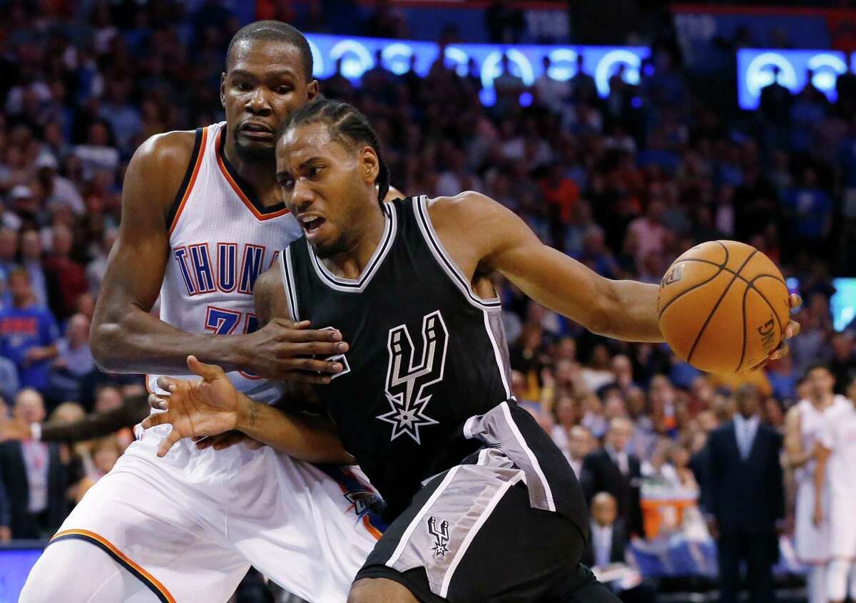 Spurs forward Kawhi Leonard drives around Oklahoma City Thunder forward Kevin Durant in the fourth quarter on Oct. 28, 2015.