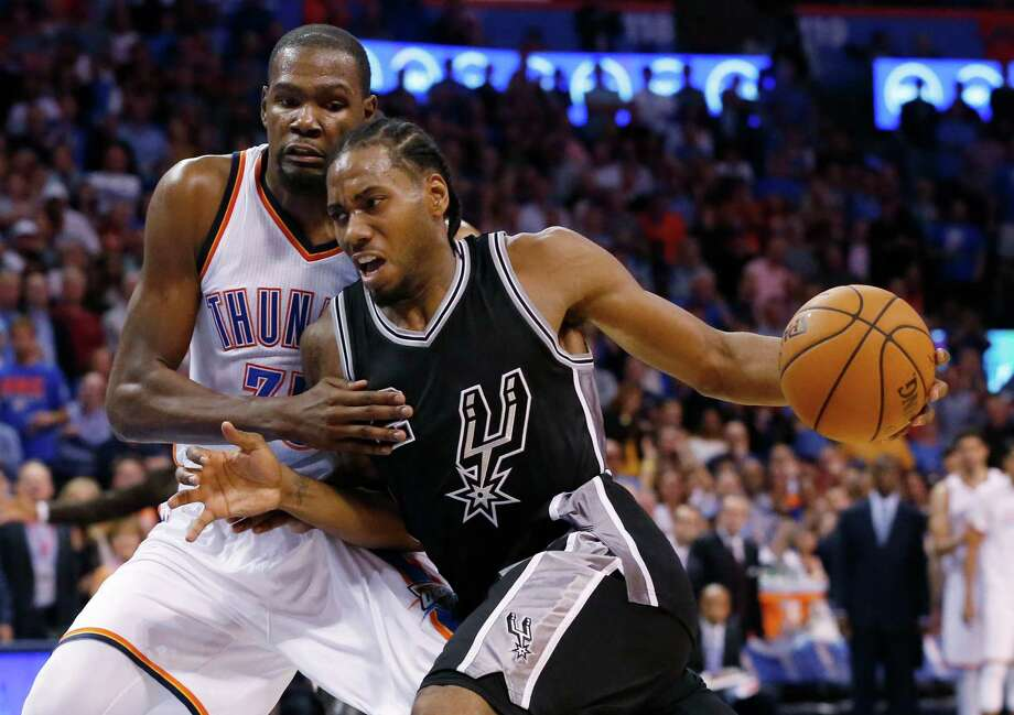 Spurs forward Kawhi Leonard drives around Oklahoma City Thunder forward Kevin Durant in the fourth quarter on Oct. 28, 2015. Photo: Sue Ogrocki /Associated Press / AP