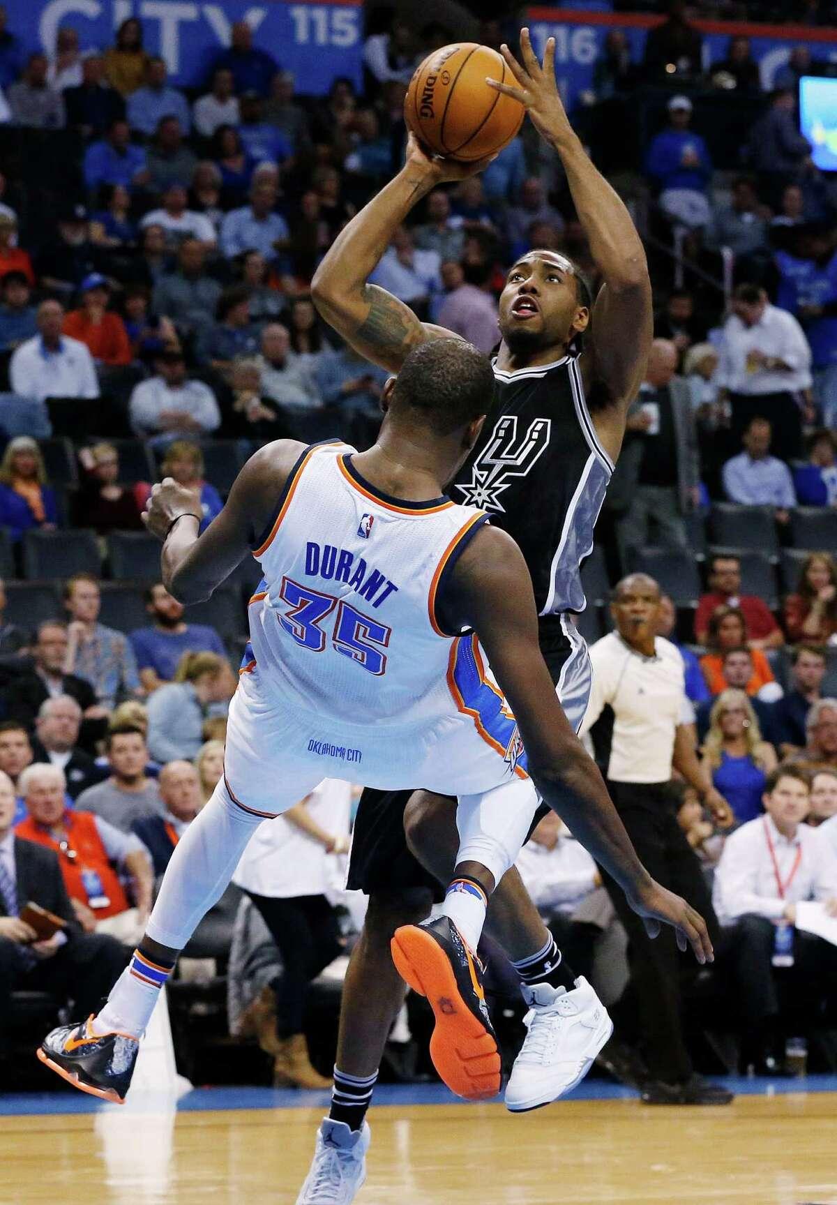 Spurs forward Kawhi Leonard is fouled by Oklahoma City Thunder forward Kevin Durant while shooting in the third quarter on Oct. 28, 2015. Oklahoma City won 112-106.