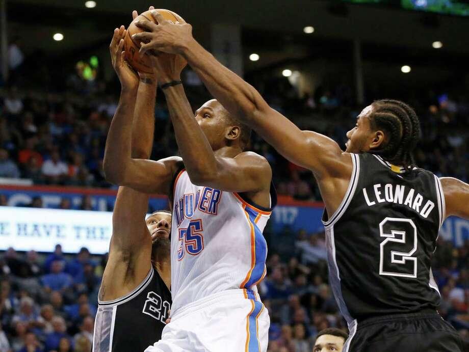 Oklahoma City Thunder forward Kevin Durant (35) is double-teamed by San Antonio Spurs forward Tim Duncan (21) and forward Kawhi Leonard (2) in the second quarter in Oklahoma City on Oct. 28, 2015. Photo: Sue Ogrocki /Associated Press / AP