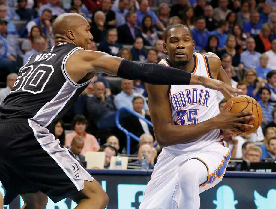 San Antonio Spurs forward David West (30) defends as Oklahoma City Thunder forward Kevin Durant (35) drives to the basket in the second quarter of an NBA basketball game in Oklahoma City, Wednesday, Oct. 28, 2015. (AP Photo/Sue Ogrocki) Photo: Sue Ogrocki, STF / Associated Press / AP