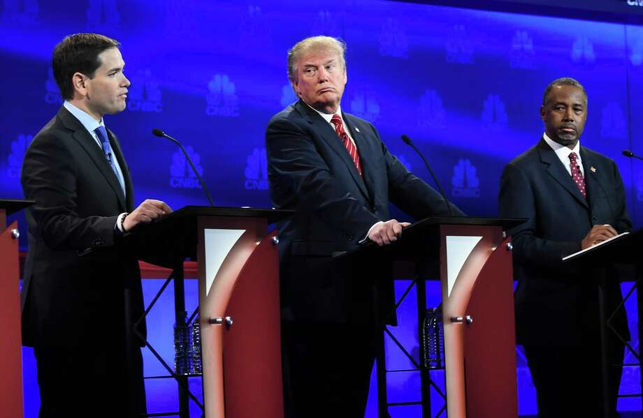 Republican Presidential hopeful Marco Rubio (L) speaks as Donald Trump (C) and Ben Carson look on during the CNBC Republican Presidential Debate, October 28, 2015 at the Coors Event Center at the University of Colorado in Boulder, Colorado. AFP PHOTO/ ROBYN BECKROBYN BECK/AFP/Getty Images ORG XMIT: 579062387 Photo: ROBYN BECK / AFP