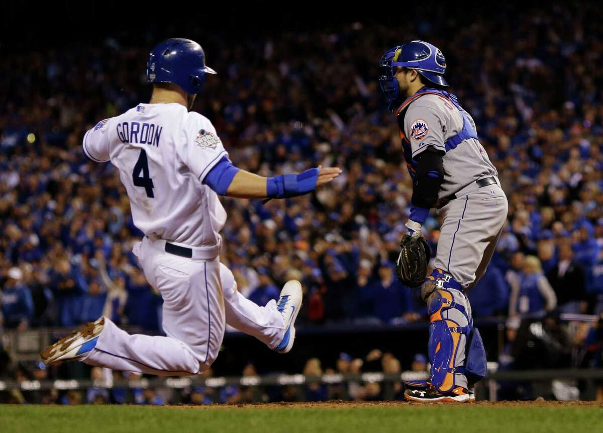 New York Mets catcher Travis d'Arnaud waits for the throw as Kansas City Royals' Alex Gordon (4) slides in to score on an RBI single by Alcides Escobar during the fifth inning of Game 2 of the Major League Baseball against the New York Mets World Series Wednesday, Oct. 28, 2015, in Kansas City, Mo. (AP Photo/Matt Slocum) ORG XMIT: WS122