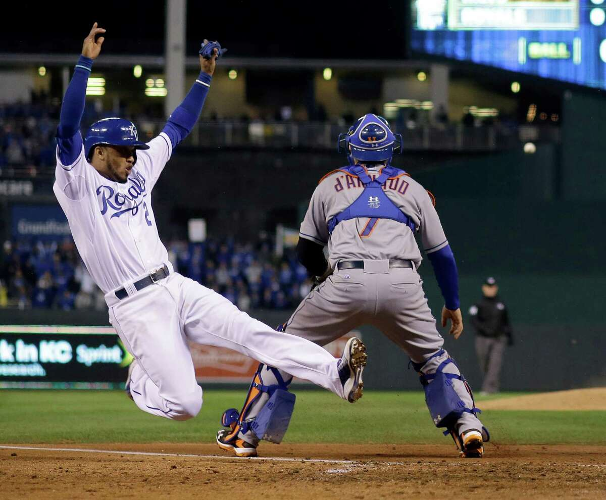 Kansas City Royals' Alcides Escobar, left, scores past New York Mets catcher Travis d'Arnaud on a single by Eric Hosmer during the fifth inning of Game 2 of the Major League Baseball World Series Wednesday, Oct. 28, 2015, in Kansas City, Mo. (AP Photo/Matt Slocum) ORG XMIT: WS323