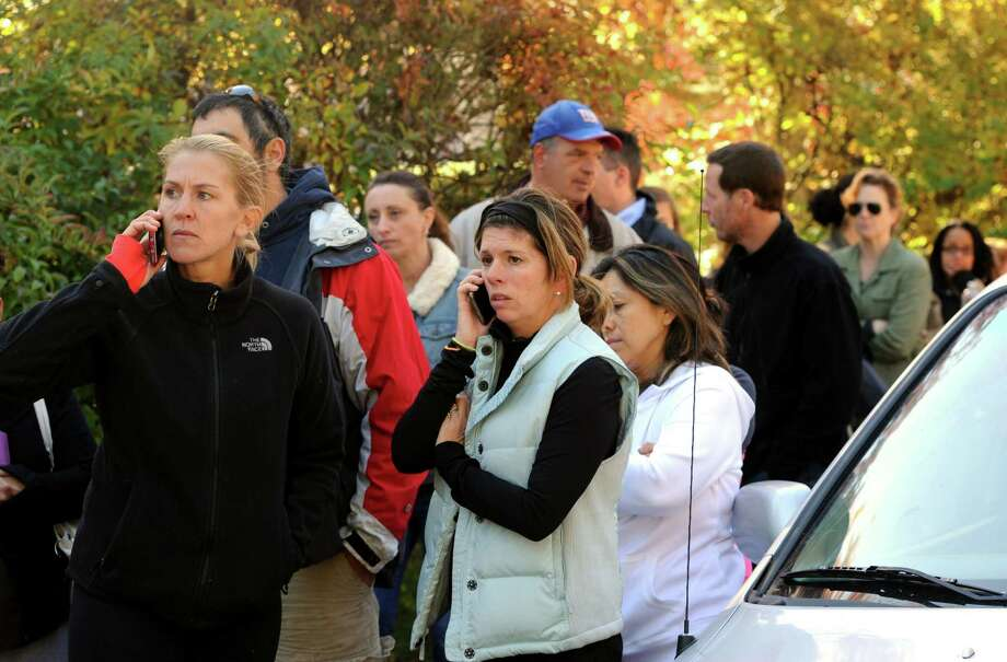 Parents gather at Holland Hill School in Fairfield. to get information and to pick up their children after a threat forced the school into lockdown on Friday, Oct. 23. Photo: Cathy Zuraw / Hearst Connecticut Media / The Connecticut Post