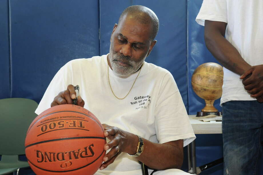 Former NBA player Luther (Ticky) Burden, an Albany native, signs a basketball while visiting Trinity Alliance on Friday, June 21, 2013 in Albany, N.Y. Burden started playing basketball in this gym as a youth. (Lori Van Buren / Times Union) Photo: Lori Van Buren / 00022902A
