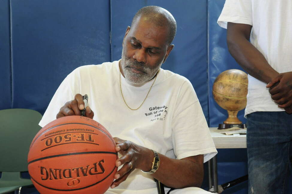 Former NBA player Luther (Ticky) Burden, an Albany native, signs a basketball while visiting Trinity Alliance on Friday, June 21, 2013 in Albany, N.Y. Burden started playing basketball in this gym as a youth. (Lori Van Buren / Times Union)