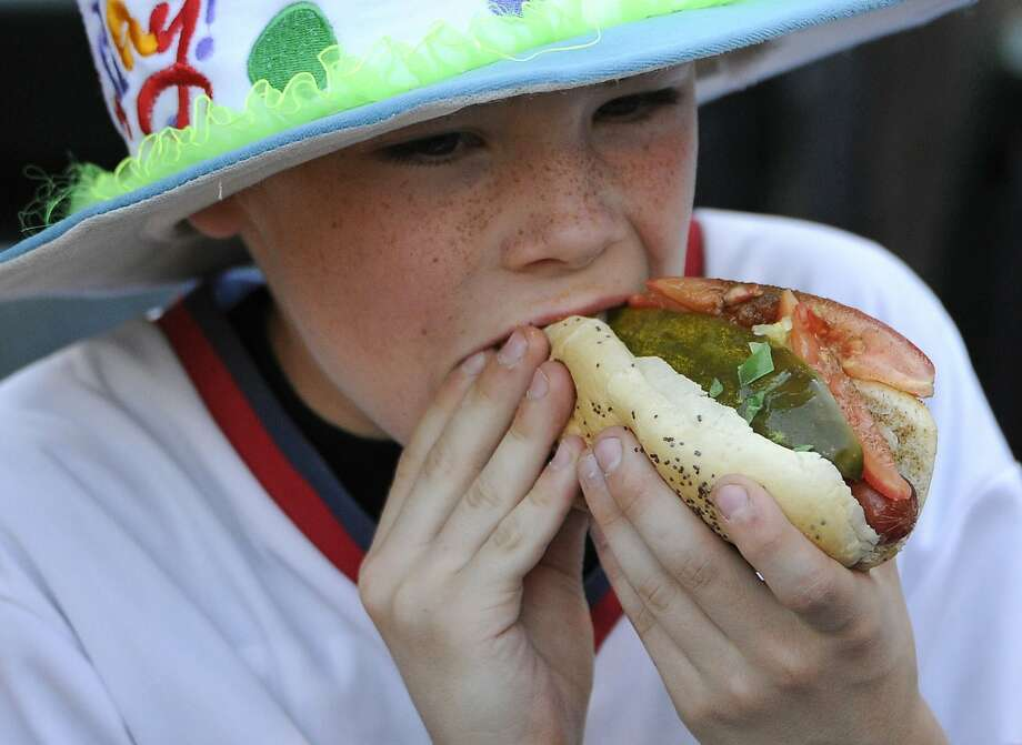 """In this June 9, 2015 file photo, a young fan eats a hot dog before a baseball game between the Chicago White Sox and the Houston Astros, in Chicago. On the eve of the World Series, where hot dogs are a staple in the stands, the World Health Organization on Monday, Oct. 26, 2015 labeled the all-American wiener, bacon and other processed meats as being """"carcinogenic to humans."""" (AP Photo/David Banks, File) Photo: David Banks, Associated Press"""