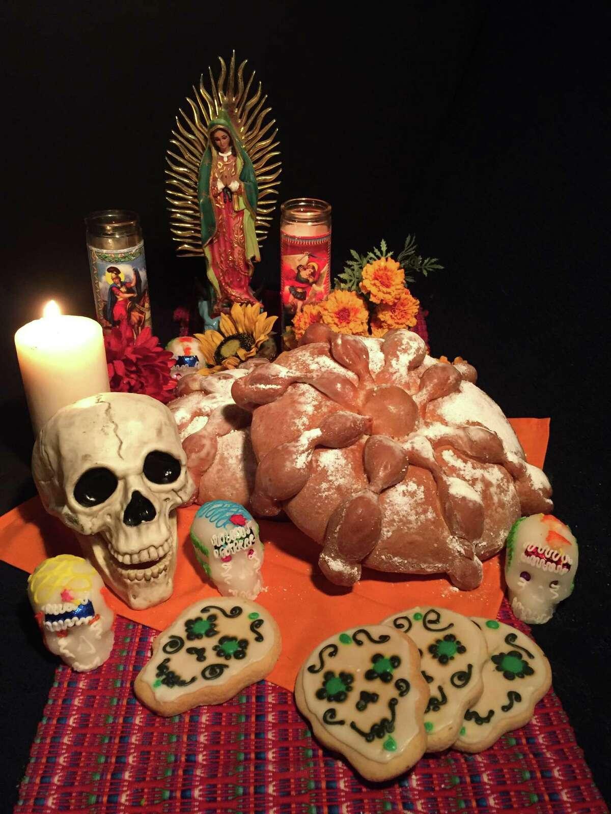 A display for Día de los Muertos: pan de muerto, candles, cookies, sugar skulls and Our Lady of Guadalupe
