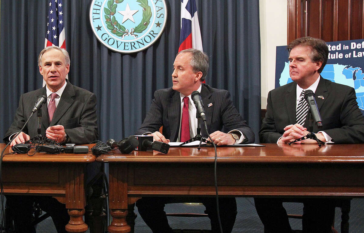 Gov. Greg Abbott, talks to reporters as Attorney General Ken Paxton listens at a news conference at the State Capitol in February. Paxton's legal woes now include a threat of disbarment because of his actions after the Supreme Court ruled on gay marriage. But if he warrants investigation by the State Bar, why not Abbott, who acted similarly?