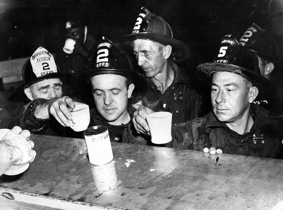 San Francisco firefighters take a break after controlling a waterfront fire on Oct. 5, 1959.  Photo: Chronicle File, The Chronicle