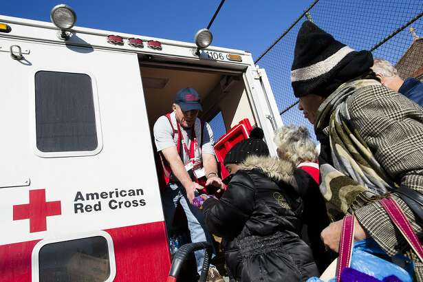 FILE - In this Friday, Nov. 9, 2012 file photo, a member of the American Red Cross distributes food to residents of Coney Island affected by Superstorm Sandy in the Brooklyn borough of New York. A year after receiving huge sums to respond to Superstorm Sandy, the American Red Cross experienced a 32 percent drop in charitable donations in 2014. It fell from ninth to 21st place among the nation's best-supported nonprofits _ its lowest ranking since The Chronicle of Philanthropy began an annual survey in 1991. (AP Photo/John Minchillo)