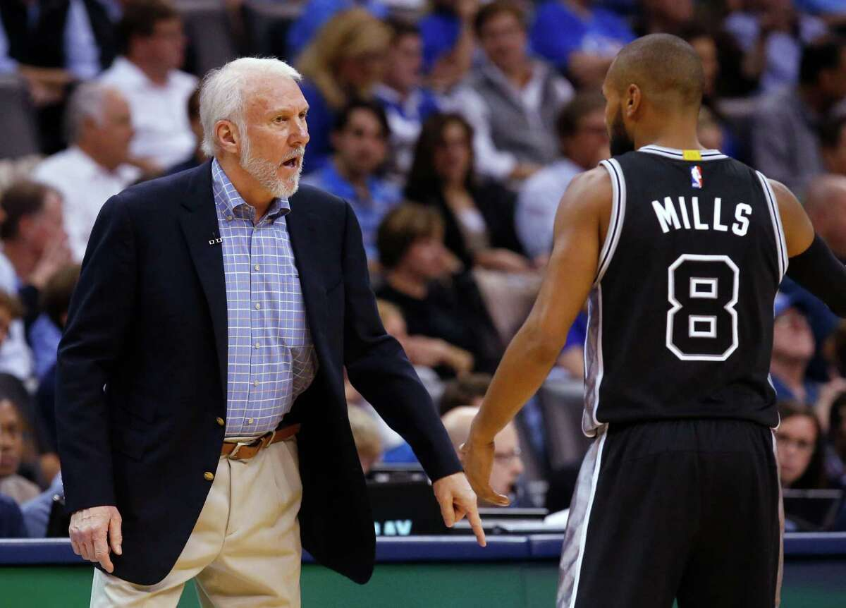 Spurs coach Gregg Popovich talks with guard Patty Mills during the second quarter against the Oklahoma City Thunder.