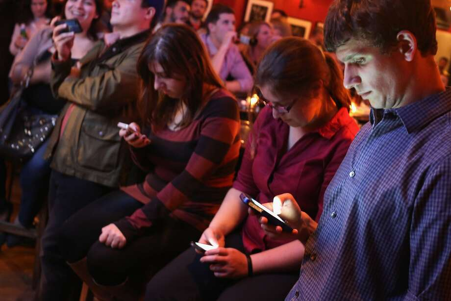 Young people often check social media during events, like these folks do during the Democratic debate. Photo: Chip Somodevilla, Getty Images