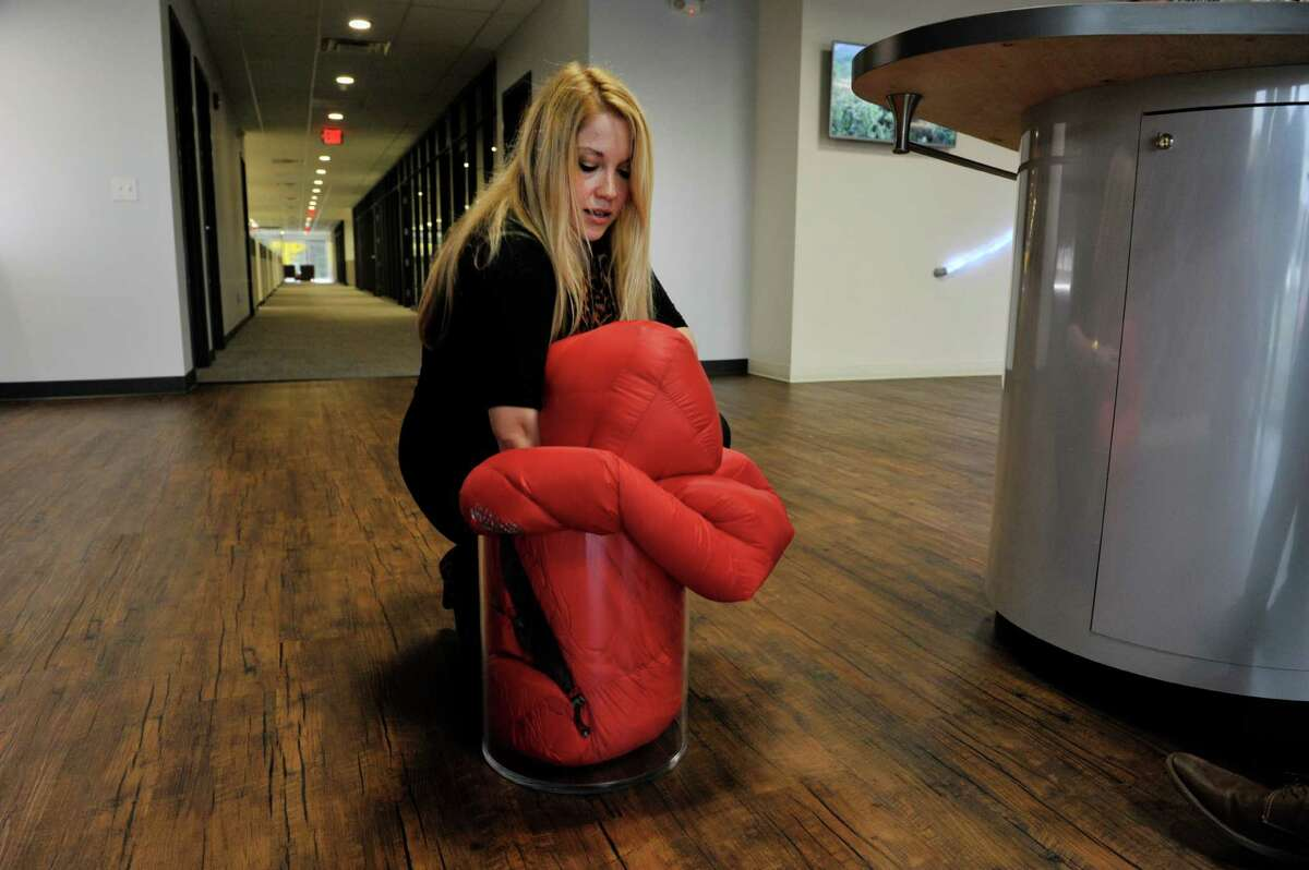 Victoria Lee, creative services manager at PrimaLoft, uses a sleeping bag filled with PrimaLoft to demonstrate how compressible it is during a tour of the showroom at the company's headquarters on Thursday, Oct. 29, 2015, in Latham, N.Y. (Paul Buckowski / Times Union)
