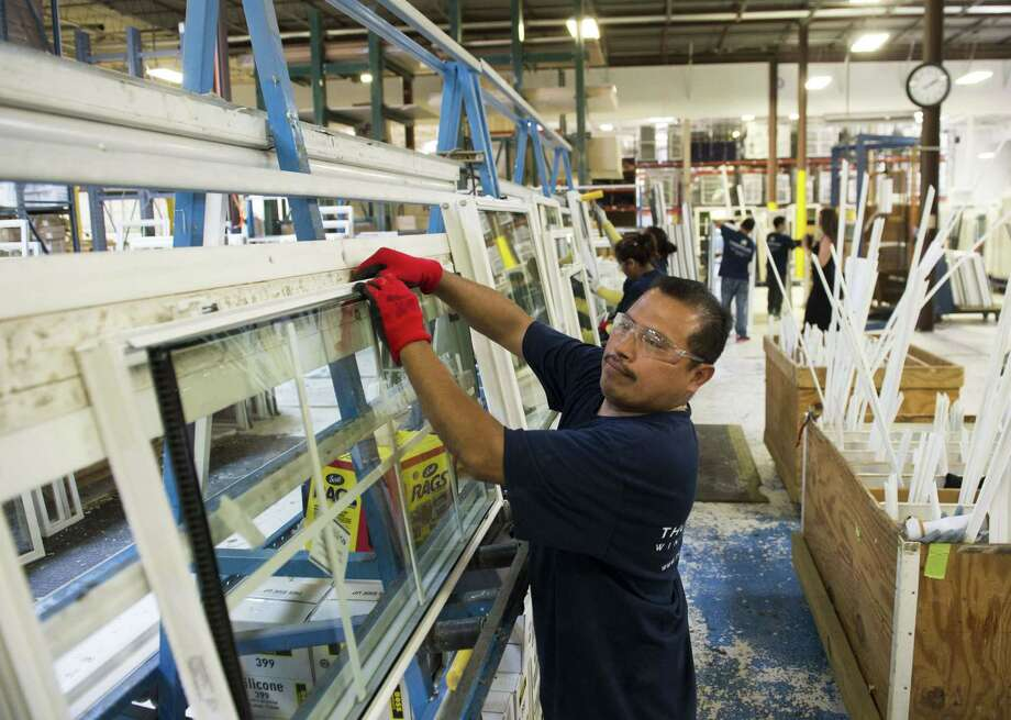 (FILES) A file picture taken on June 8, 2015 shows an employee builds a window at the Thompson Creek Window Company factory in Landover, Maryland. The US economy grew at a slower pace in the third quarter as exports and private inventory investment fell, but crucial consumer spending remained strong, the Commerce Department said Thursday. Consumer spending rose 3.2 percent in the third quarter, a tad less than the second quarter's increase. But disposable personal income jumped 3.5 percent, nearly three times the gain in the second quarter, suggesting a promising set-up to the upcoming holiday shopping season. AFP PHOTO / SAUL LOEBSAUL LOEB/AFP/Getty Images ORG XMIT: US econom Photo: SAUL LOEB / AFP