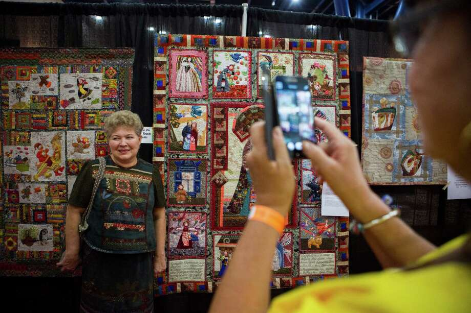 Natalia Vihrova, center, a top quilter from Siberia is photographed by a quilt enthusiast in front of her creation at the International Quilt Festival in Houston taking place at the George R. Brown Convention Center, Thursday, Oct. 29, 2015. ( Marie D. De Jesus / Houston Chronicle ) Photo: Marie D. De Jesus, Staff / © 2015 Houston Chronicle
