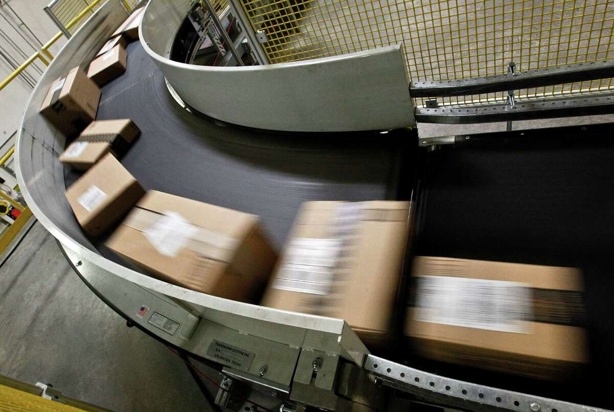 FILE - in this Monday, Nov. 26, 2012, file photo. packages move along a conveyor belt at the Amazon.com 1.2 million square foot fulfillment center, in Phoenix. (AP Photo/Ross D. Franklin, File)