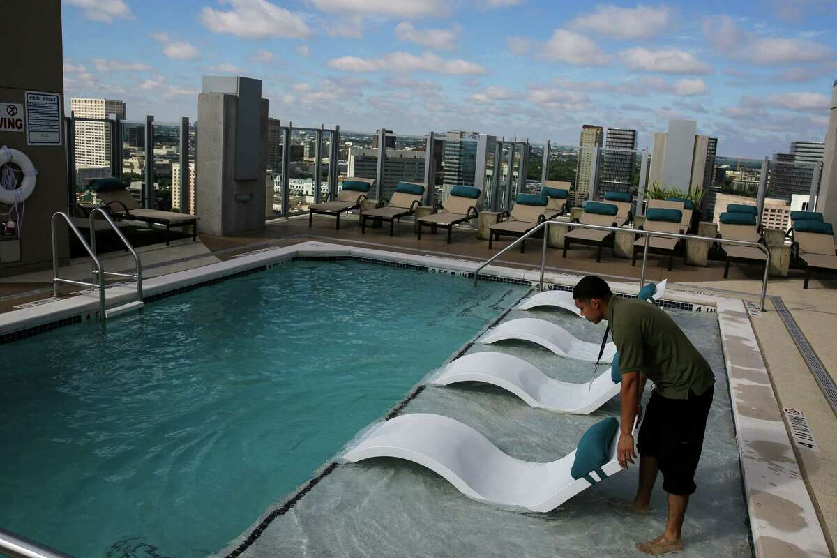 SkyHouse River Oaks employee Fredi Matute arranges pool chairs on the rooftop at the newly built high rise in the Galleria area Tuesday, Oct. 27, 2015, in Houston. Residential housing now surpasses retail in terms of how land is distributed in the neighborhood. The apartment building, which opened in late July, is currently 16 percent leased. (Michael Ciaglo / Houston Chronicle)