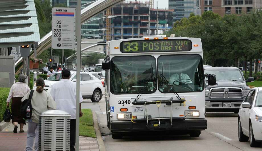 Passengers wait to board a Metro bus stop along Post Oak near Westheimer on Sept. 18, 2014. Photo: Melissa Phillip, Staff / © 2014  Houston Chronicle