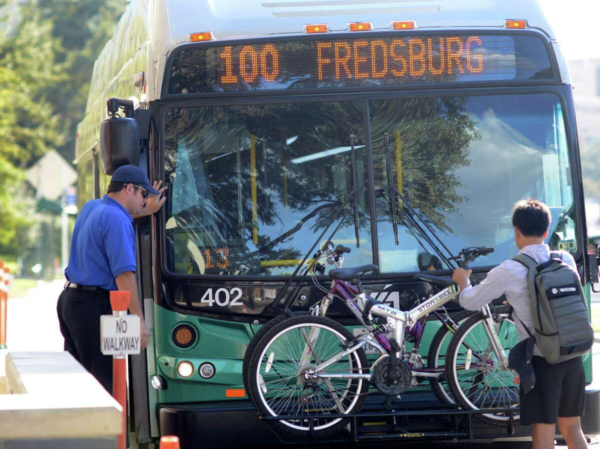 A man places his bicycle on a VIA Primo rapid transit bus along Medical Drive on Wednesday, Oct. 8, 2014.