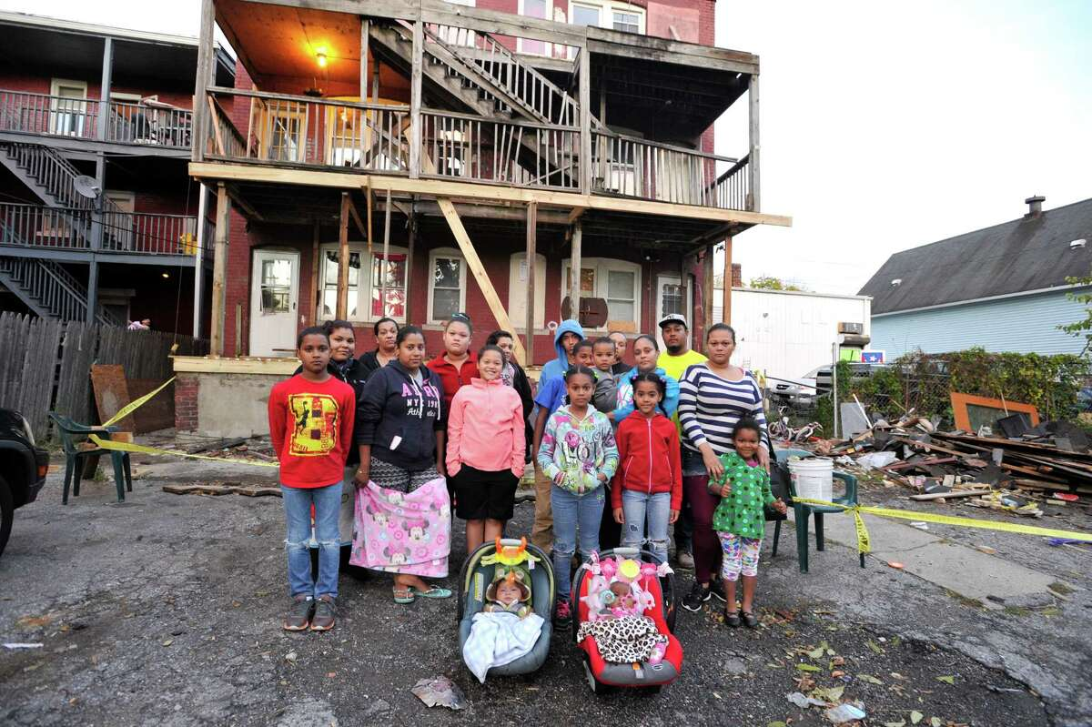 Six families were displaced last month when the back staircase of the building at 265 Greenwich Ave. broke, injuring one woman. The city shut down the building while the staircase and other repairs are being done. From left, Engers De La Cruz, Martha Herrera, Ana Polanco, Scarlet Garcia, Tania Cuevas, Diana Cuevas, Dulce Rodriguez, Waldy Cordero, Brian De La Cruz, Ayeleen Cuevas Cordero, Yendri Cuevas Cordero, Ana Cordero, Nilka Cuevas, Mary Cuevas Cordero, Ayennys Cuevas, Alba Cuevas, Alexa Cuevas and infants Jacob Rodriguez and Dulce Gonzalez, front, are only some of those displaced.