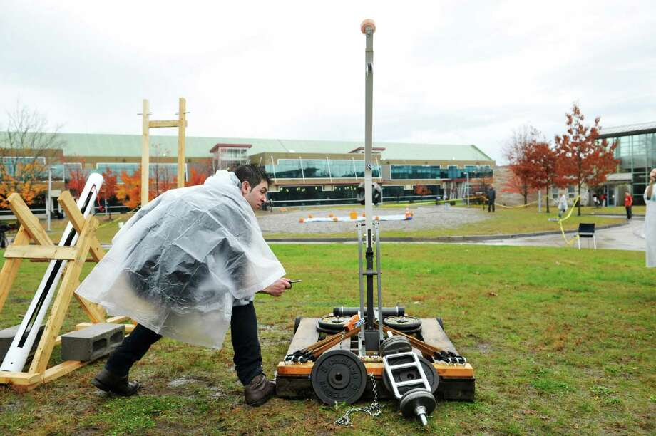 Student Devon Gerstenberger launches a pumpkin from his team's catapult during Hudson Valley Community College Pumpkin Palooza event on Thursday, Oct. 29, 2015, in Troy, N.Y.  Engineering Science students launched pumpkins with catapults they designed and built.  The teams received points for getting a pumpkin into a bucket or close to it.    (Paul Buckowski / Times Union) Photo: PAUL BUCKOWSKI / 00033985A