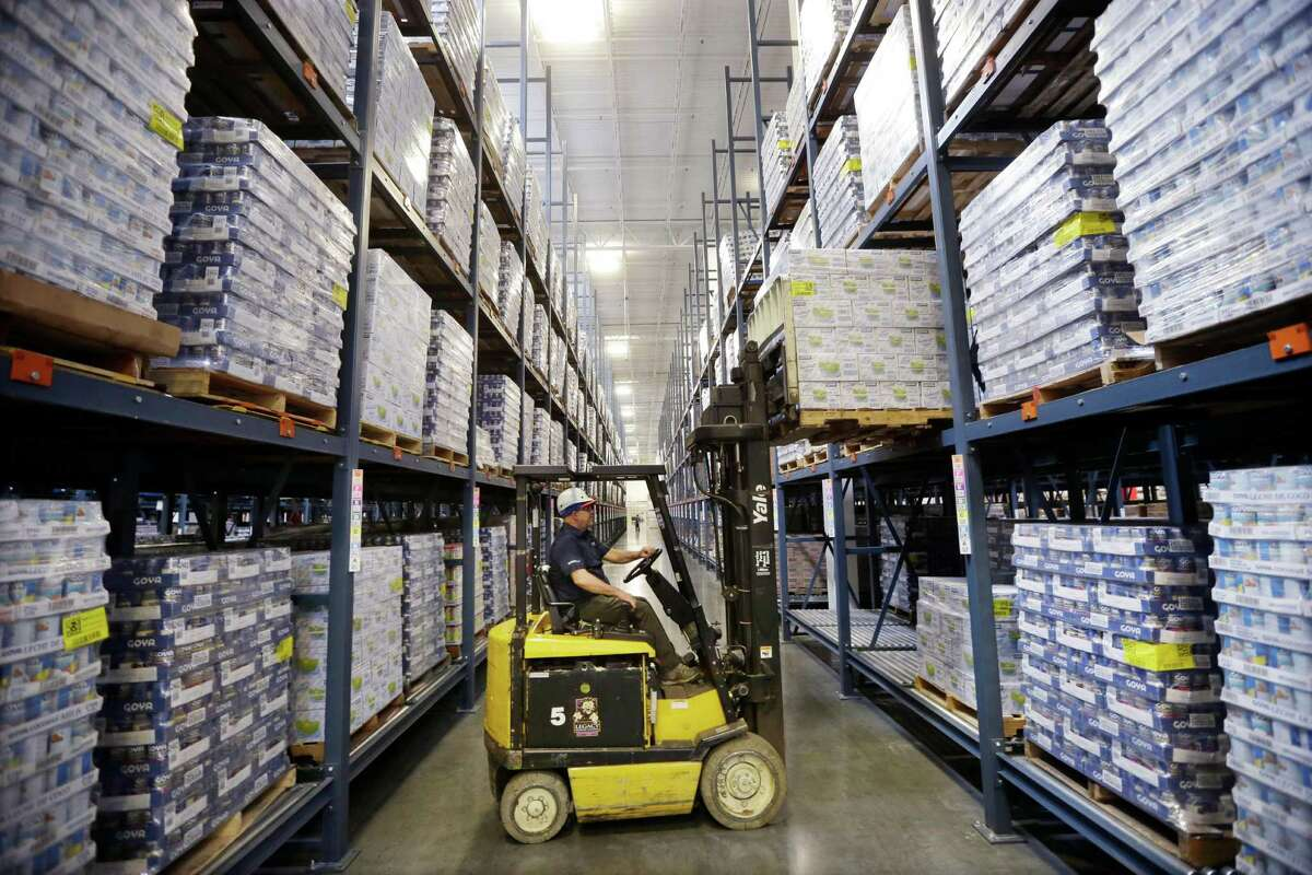 A worker lifts Goya Foods products in a warehouse at the corporate headquarters in Jersey City, N.J. Much of the downshift in third quarter's economic growth was because of slower inventory accumulation, as businesses let stockpiles of goods in warehouses and on store shelves unwind.