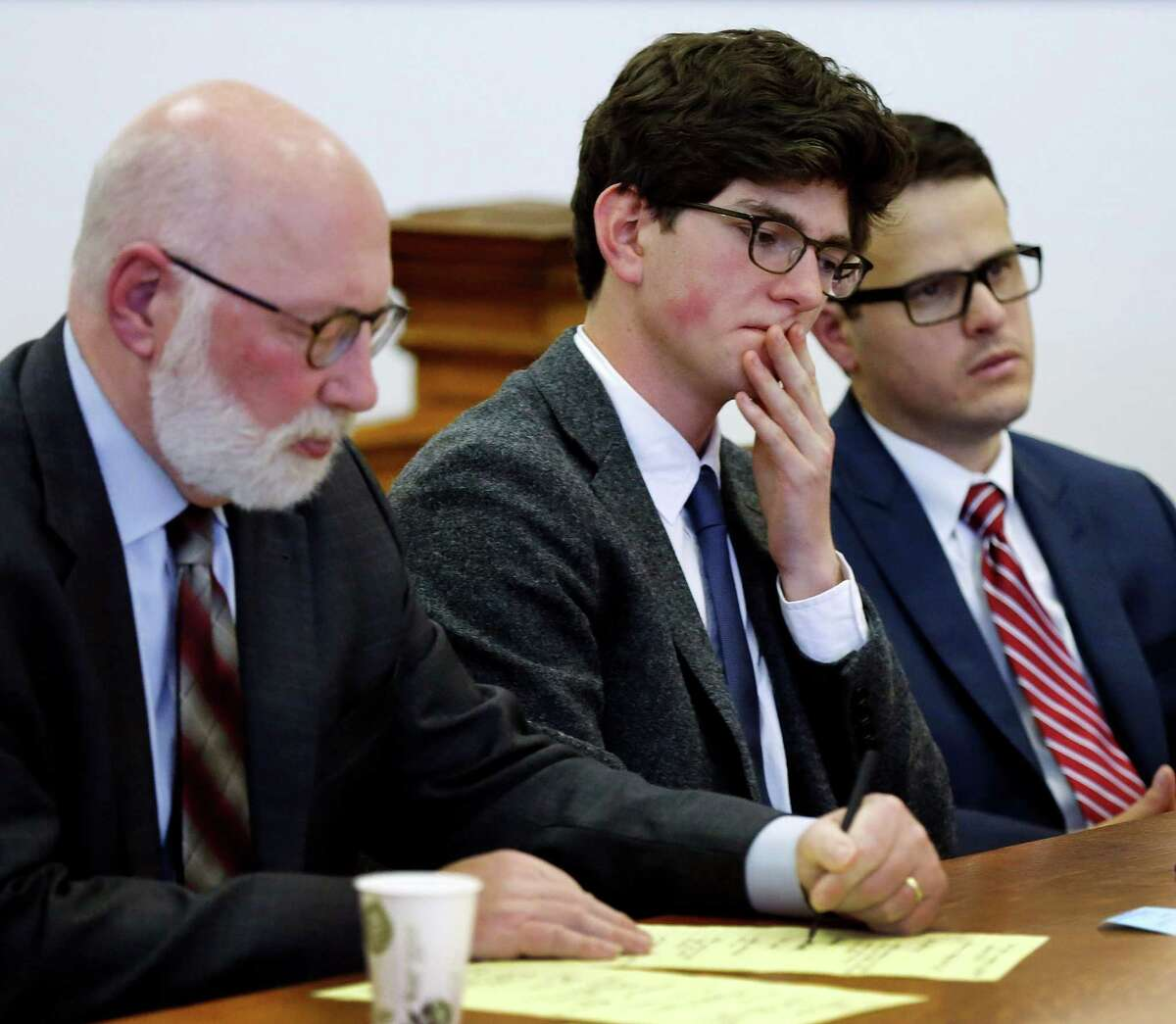 Owen Labrie, center, listens to a recorded statement from his victim with his lawyer J.W. Carney, left, and Sam Zaganjoir before being sentenced in Merrimack County Superior Court Thursday, Oct. 29, 2015, in Concord, N.H. The graduate of the exclusive St. Paul?'s School was sentenced to a year in jail for sexually assaulting a 15-year-old freshman girl as part of a tradition in which upperclassmen competed to rack up sexual conquests. Labrie was allowed to remain free on bail while he appeals his conviction. (AP Photo/Jim Cole, Pool)