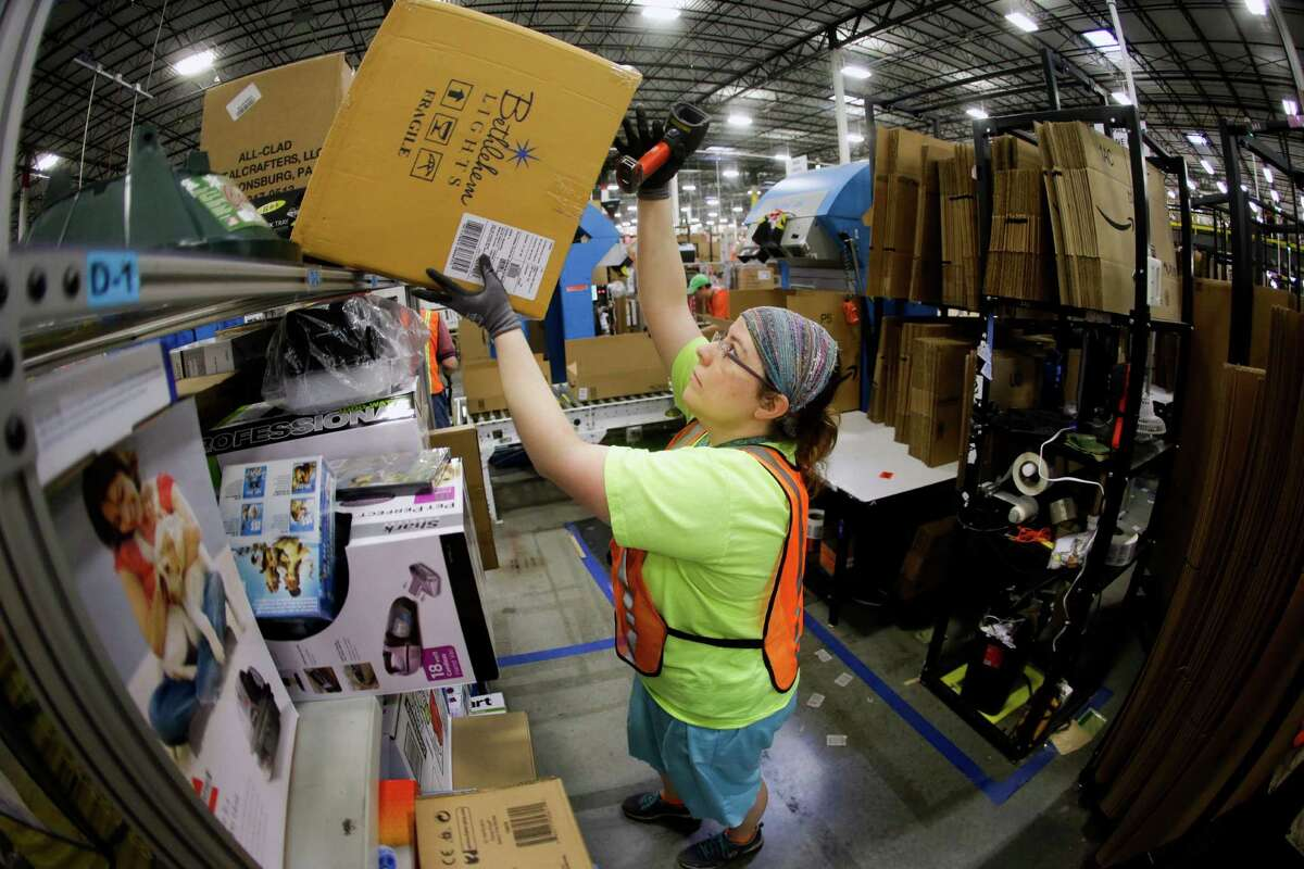 Ashley Merritt fills an order for shipping at the Amazon center during last year's Cyber Monday. Cyber Monday is traditionally the busiest online shopping day of the year.