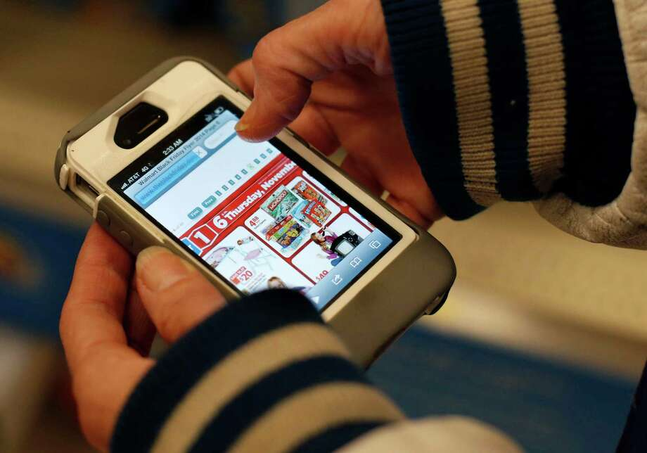 A shopper uses her iPhone to compare prices at Wal-Mart while shopping at a Target. Wal-Mart promises it won't be beat on prices this holiday season.  Photo: Robert F. Bukaty, STF / AP