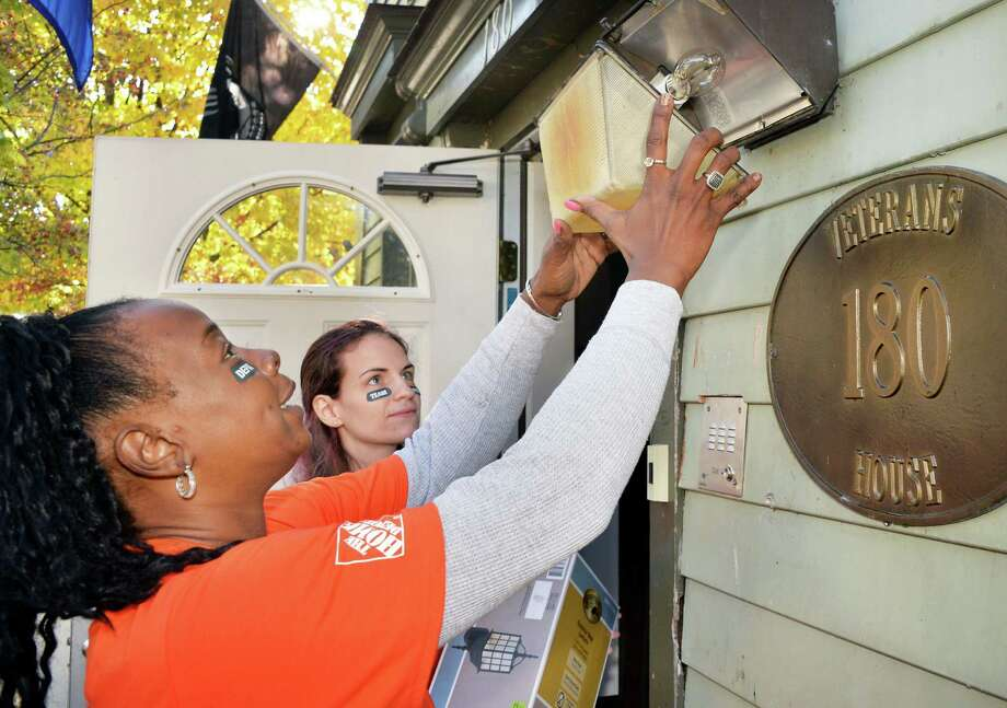 Home Depot cashiers Sala Galloway, left, and Lindsay Adams ready an old light fixture for replacement as more than 25 Home Depot volunteers work to rehab the Veterans House Thursday Oct. 29, 2015 in Albany, NY.  (John Carl D'Annibale / Times Union) Photo: John Carl D'Annibale / 00033995A
