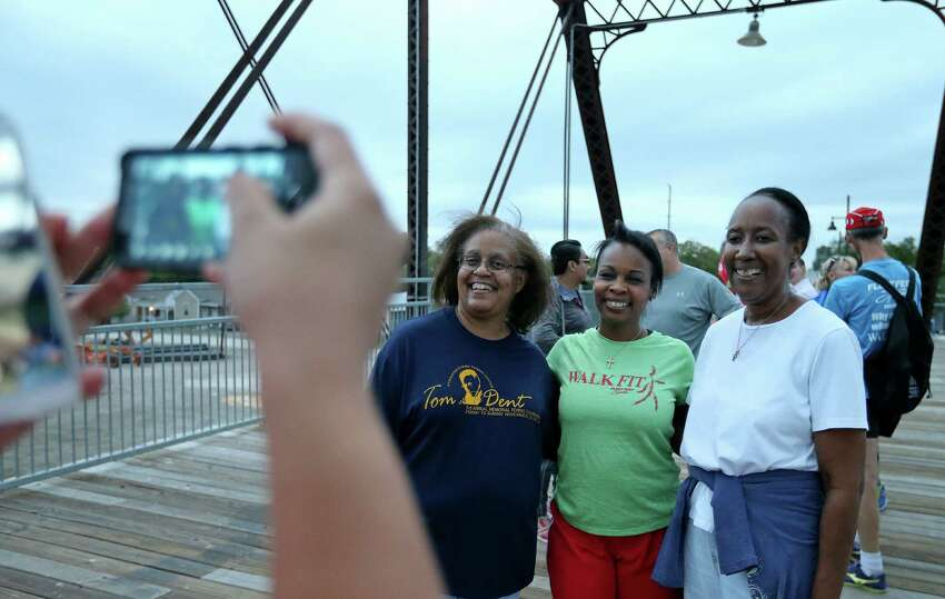 Mayor Ivy Taylor (center) poses for photos with Fauvette Jones (left) and Phyllis McNair on the Hays Street Bridge after their 1.7 mile walk from Alamo Beer Co. to VFW Post 76, the Riverwalk Museum Reach, then back to Alamo Beer Co. Thursday Oct. 29, 2015. Members of the veterans group Team Red, White and Blue, Fleet Feet?•s WalkFIT group, and others participated in the walk.