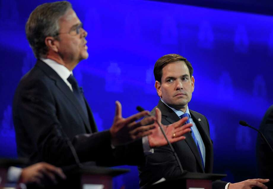 Marco Rubio, right, watches as Jeb Bush speaks during the CNBC Republican presidential debate Wednesday at the University of Colorado in Boulder, Colo. Although political partners in Florida, the two have transitioned into fighting mode. Photo: Mark J. Terrill, STF / AP