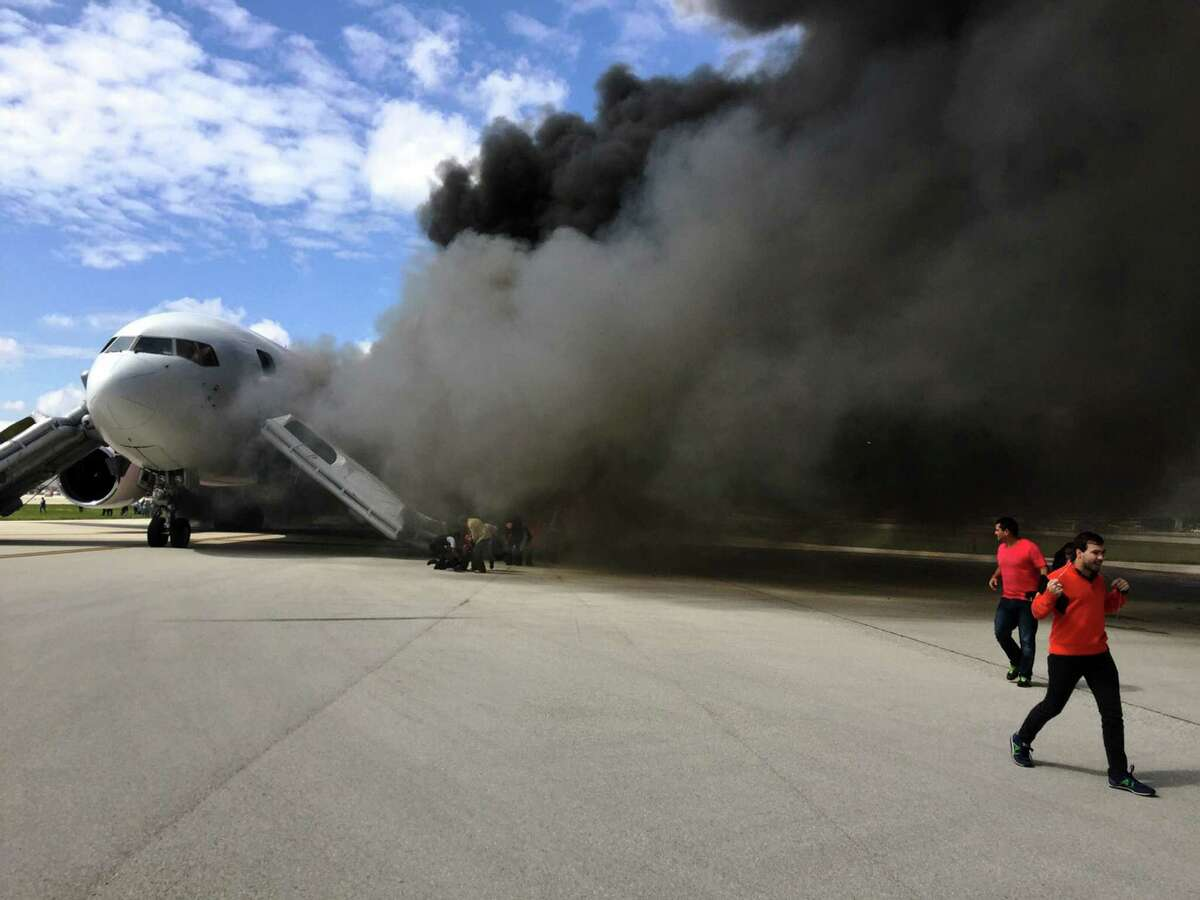 Passengers are evacuated from a plane on fire at Fort Lauderdale/ Hollywood International Airport. The Dynamic Airways flight was scheduled to fly to Caracas, Venezuela. The airline also flies to New York and Guyana.
