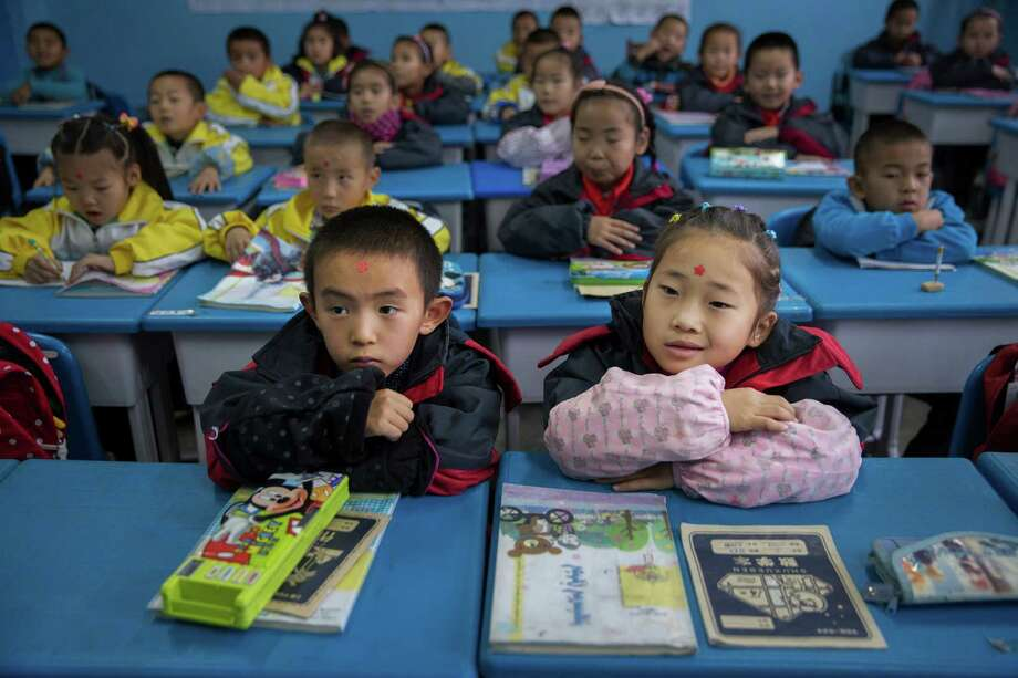 Children attend a class at a school in Qapqal, China, on Thursday, when China announced an end to the decades-old policy restricting the number of children married couples can have to one. Photo: ADAM DEAN, STR / NYTNS