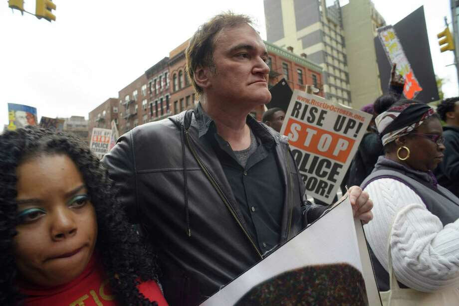 Director Quentin Tarantino, center, participates in a rally to protest against police brutality Saturday, Oct. 24, 2015, in New York. Speakers at the protest said they want to bring justice for those who were killed by police. (AP Photo/Patrick Sison) ORG XMIT: NYPS102 Photo: Patrick Sison / AP