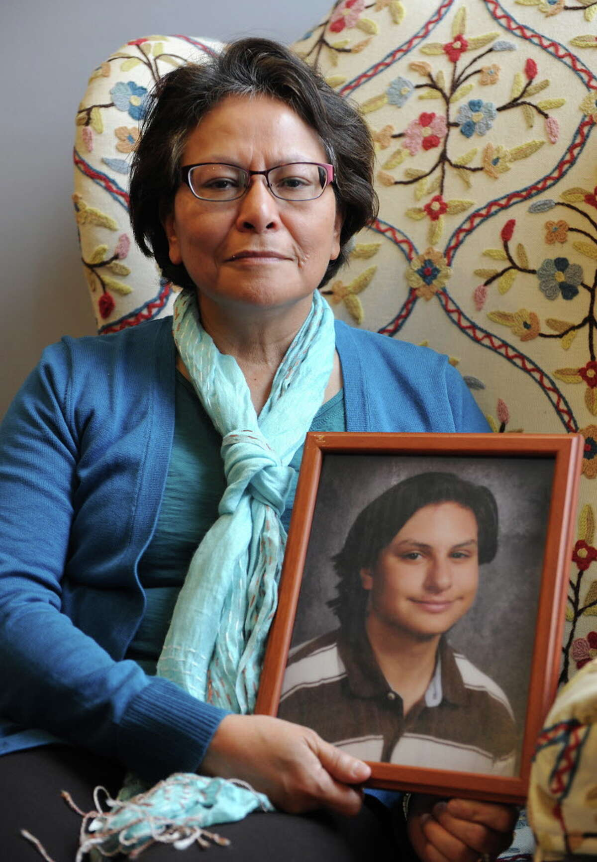 Alicia Barraza holds a framed photograph of her son in her home on Friday, Dec. 12, 2014 in Albany, N.Y. Alicia's son Benjamin Van Zandt hung himself in his prison cell last month at age 21. He had a history of mental illness and was sent to state prison at 17 for arson. (Lori Van Buren / Times Union)
