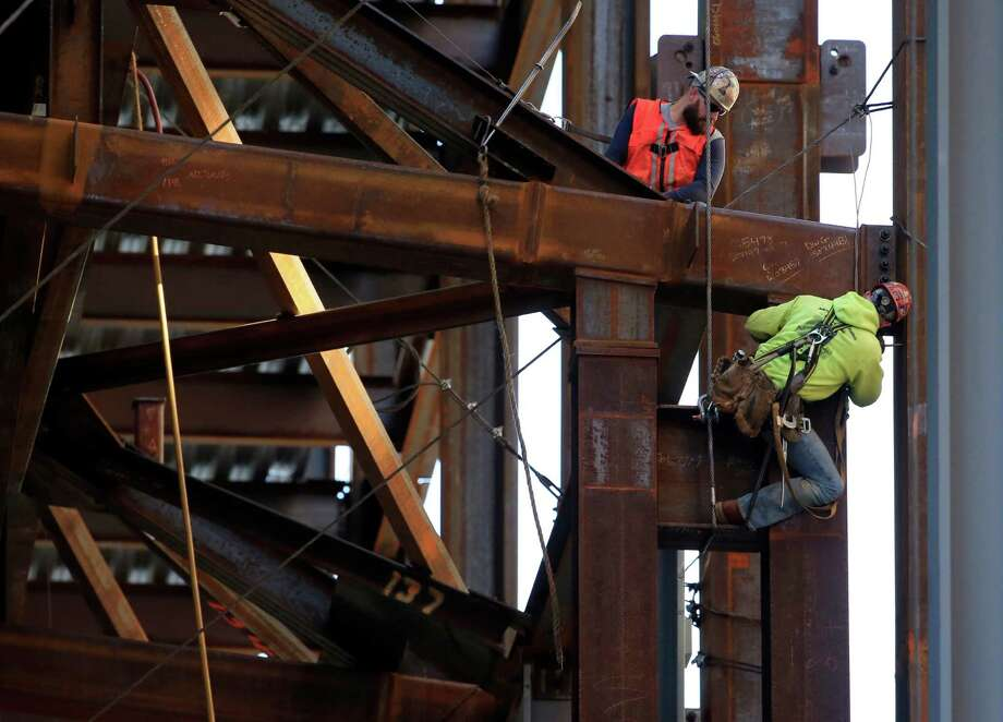 Iron workers help build the Comcast Innovation and Technology Center in Philadelphia. July, August and September's U.S. growth figures represent a marked drop from the 3.9 percent pace of expansion in the spring. quarter on Thursday, Oct. 29, 2015. (AP Photo/Matt Rourke, File) Photo: Matt Rourke, STF / AP