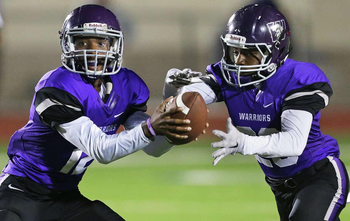 Warrior quarterback Benjamin Greene starts a handoff to running back Clarence Williams but then pulls back after eyeing the defense as Taft plays Warren at Gustafson Stadium on October 29, 2015.